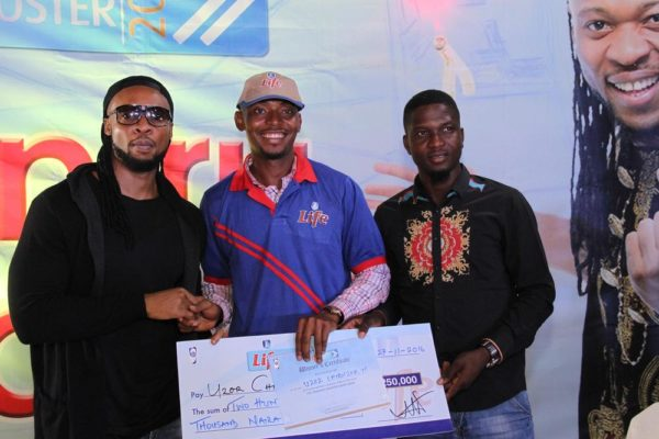Flavour, brand ambassador for Life Continental Beer, and Akinola Josiah Olufemi, Assistant Brand Manager, Regional Mainstream Brands, NB Plc presenting a cheque of N250, 000 to Uzor Chibuzor, one of the winners of the Life Progress Booster Show in Onitsha.