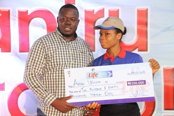 Kelvin Aladesanmi, Sales Executive, Onitsha, NB Plc presenting a cheque of N250,000 to Anita Ugochi, one of the winners of the Life Progress Booster Show in Onitsha.