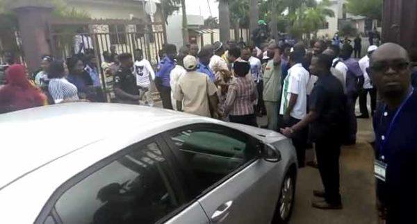 Police teargas protesting staff as they escort NHIS Boss into Premises | BellaNaija